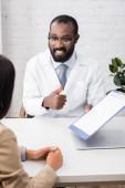 selektivní zaměření afrického amerického lékaře v brýlích ukazující palec nahoru při držení pojistného nároku formulář