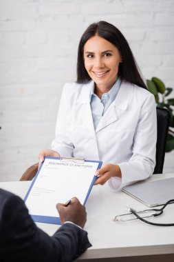 Brunette, joyful doctor holding clipboard while african american patient signing insurance claim form stock vector