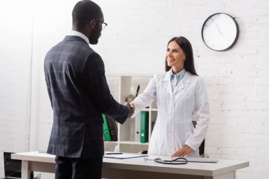 Brunette woman shaking hands with african american patient wearing suit stock vector