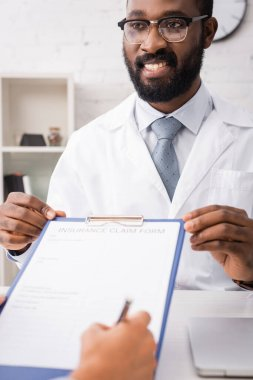 Selective focus of joyful african american doctor holding clipboard while patient signing insurance claim form stock vector