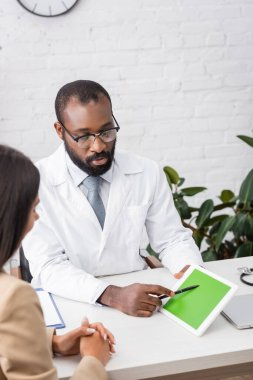 Selective focus of serious african american doctor in eyeglasses pointing with pen at digital tablet with green screen near brunette woman stock vector