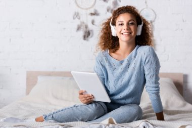 Selective focus of curly woman in headphones holding digital tablet and looking at camera on bed