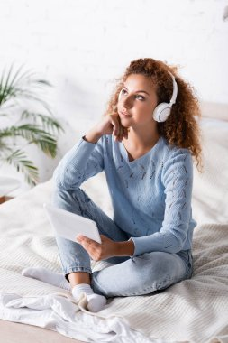 Selective focus of dreamy woman in headphones holding digital tablet on bed
