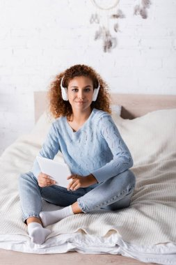 Curly woman in headphones holding digital tablet and looking at camera on bed