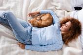 Top kilátás fiatal nő -ban pulóver feküdt mellett tabby macska az ágyban
