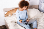 Selective focus of young woman holding credit card and using laptop near tabby cat on bed