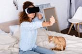 Selektiver Fokus der Frau, die Videospiel im vr-Headset in der Nähe von Katze im Schlafzimmer spielt