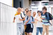 Photo selective focus of excited multicultural classmates with backpacks running along school corridor