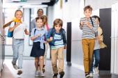 Aufgeregte multikulturelle Schüler laufen auf Schulflur mit Lehrer im Hintergrund