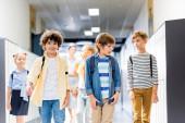 multikulturális iskolások sétálnak az iskolai folyosón tanárral a háttérben