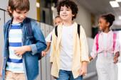 vzrušené multikulturní školáci procházky po školní chodbě