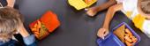 Ansicht von multikulturellen Schülern in der Nähe von Lunchboxen mit Sandwiches und frischen Karotten, horizontales Bild