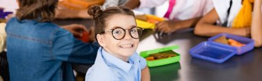 selective focus of excited schoolgirl in eyeglasses looking at camera near classmates and lunch boxes, website header