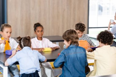 schoolgirl pointing with finger while sitting with multicultural classmates in school dining room