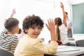 Selektiver Fokus eines arabischen Schülers mit der Hand in der Luft, der in die Kamera in der Nähe multikultureller Mitschüler blickt