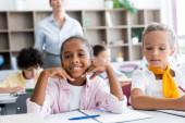 Selective focus of african american schoolgirl looking at camera near classmates and teacher in school