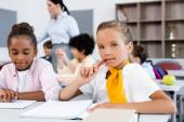 Selective focus of schoolgirl looking at camera near african american friend at desk in school