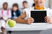 Vágott kilátás iskolás lány gazdaság digitális tabletta üres képernyővel közel alma az asztalon