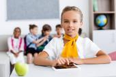 Selektivní zaměření školačky pomocí digitálního tabletu v blízkosti jablek a multikulturních spolužáků ve třídě