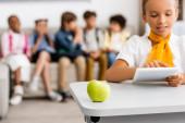Selektivní zaměření čerstvého jablka na stole poblíž školačky pomocí digitálního tabletu ve třídě