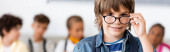 Panoramakonzept des Schülers mit Brille und Blick auf die Kamera in der Schule