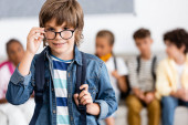 Photo Selective focus of schoolboy with backpack and eyeglasses in classroom