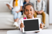 Photo Selective focus of african american schoolgirl showing digital tablet with blank screen at desk