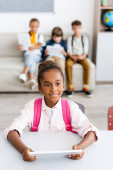Photo Selective focus of african american schoolgirl with backpack holding digital tablet at desk near friends in classroom