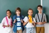 Multikulturní školáci s batohy při pohledu na kameru u tabule