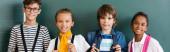 Panoráma felvétel többnemzetiségű iskolás gyerekek nézi kamera közelében táblagép