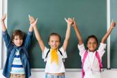 Multietnické školáci ukazují souhlas gesto v blízkosti tabuli