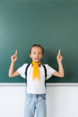 Vzrušená školačka s batohem ukazujícím prsty na tabuli