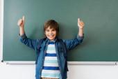 Iskolásfiú hátizsákkal mutatja hüvelykujját a zöld tábla közelében