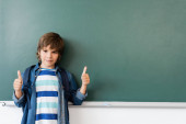 Schoolboy showing thumbs up while standing near green chalkboard