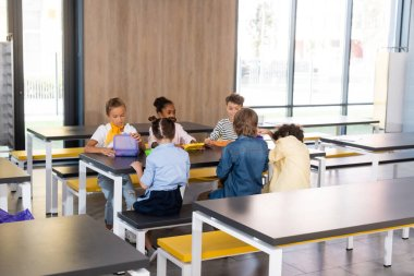 multicultural pupils sitting in school canteen during dinner brake