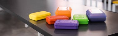 horizontal image of colorful plastic lunch boxes on table in school dining room