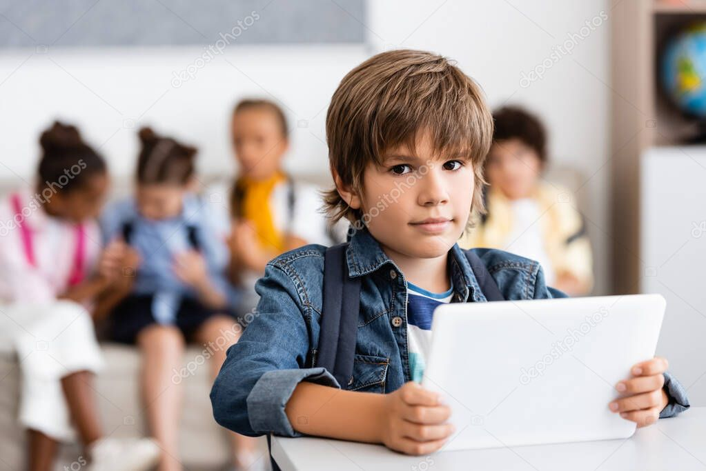 Selective focus of schoolboy holding digital tablet and looking at camera at desk in classroom stock vector