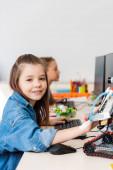 Szelektív fókusz iskolás nézi kamera közelében robot és számítógépek ősiskolában