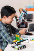 Photo Selective focus of asian schoolboy holding building block near robots in classroom