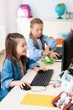 Selective focus of schoolgirls using computers near robots in stem school stock vector