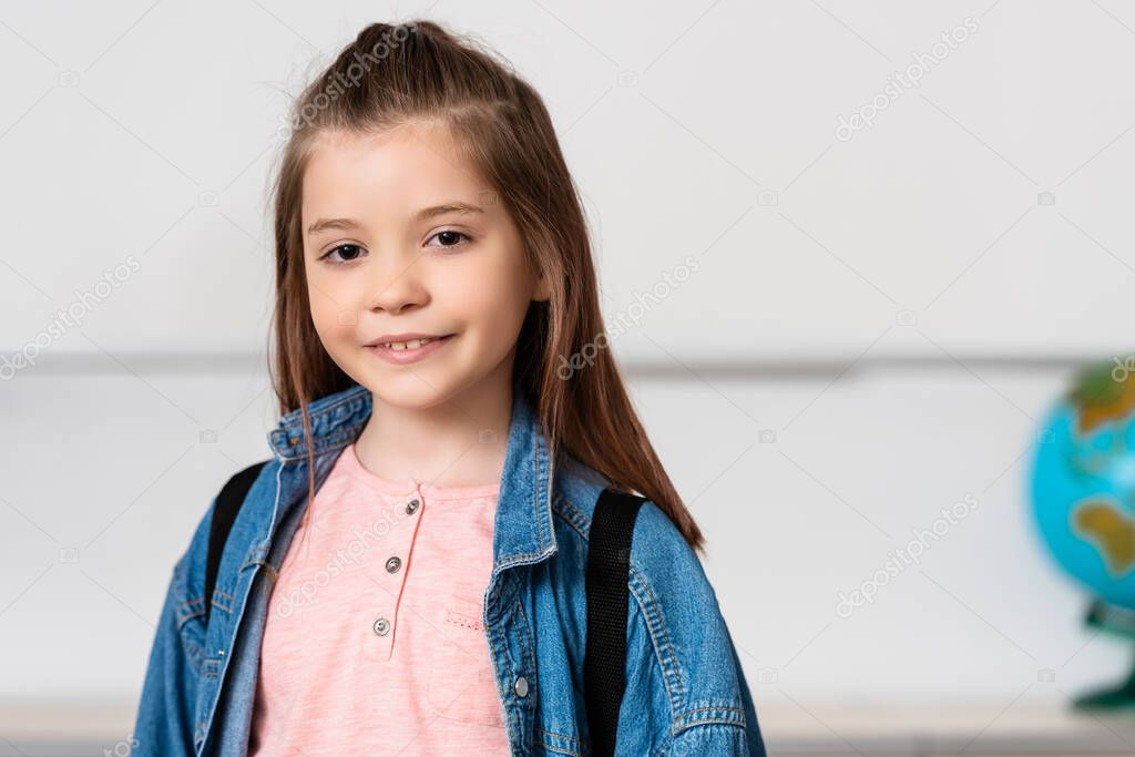 Schoolgirl with backpack looking at camera in classroom stock vector