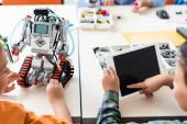 Selektivní zaměření asijského školáka pomocí digitálního tabletu v blízkosti přítele modelování robot ve škole