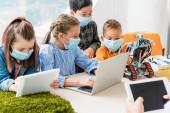 Selektiver Fokus multiethnischer Kinder in medizinischen Masken mit digitalem Tablet und Laptop in der Nähe von Lehrern und Robotern in der Schule