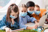 Fotografie Selective focus of multiethnic schoolkids in medical masks using gadgets while programming robot in stem school