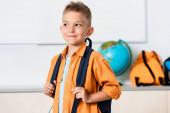 Školák drží batoh při pohledu pryč ve třídě