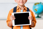 Cropped view of schoolboy holding digital tablet with blank screen