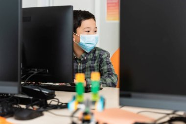 Selective focus of asian schoolboy in medical mask sitting near computers in stem school stock vector