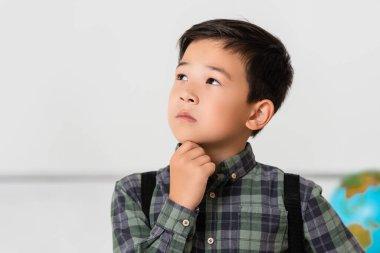 Düşünceli Asyalı okul çocuğu başka yere bakıyor.
