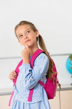Dreamy schoolgirl with backpack looking away in classroom stock vector