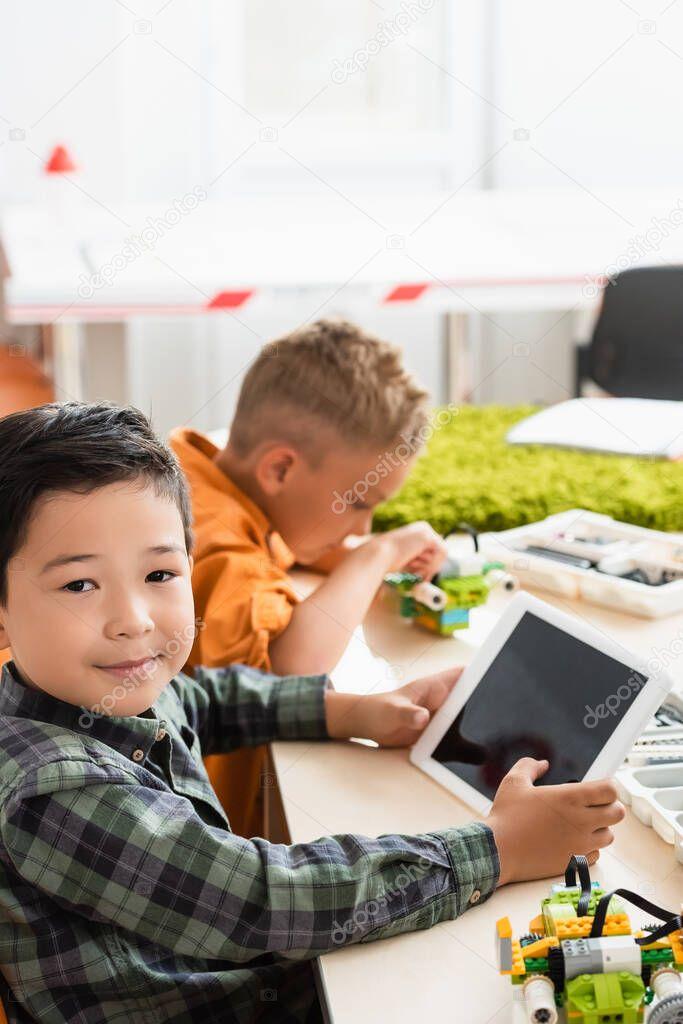 Selective focus of asian schoolboy holding digital tablet near friend modeling robot in stem school stock vector